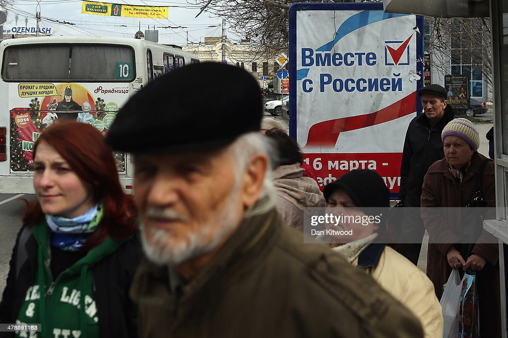Members of the public stand by a sign that reads 'Together with Russia' in Russian at a bus stop on March 14, 2014 in Simferopol, Ukraine. As the standoff between the Russian military and Ukrainian forces continues in Ukraine's Crimean peninsula, world leaders are pushing for a diplomatic solution to the escalating situation. Crimean citizens will vote in a referendum on 16 March on whether to become part of the Russian federation.