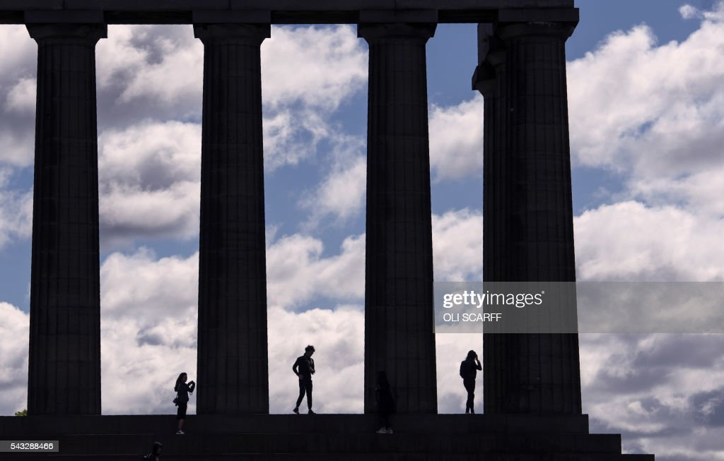 Members of the public stand on the National Monument of Scotland, on Calton Hill in the centre of Edinburgh, Scotland on June 27, 2016. British leaders battled to calm markets and the country Monday after its shock vote to leave the EU, while insisting London would be not rushed into a quick divorce. Britain's historic decision to be the first country to leave the 28-nation bloc has fuelled fears of a break-up of the United Kingdom with Scotland eyeing a new independence poll, and created turmoil in the opposition Labour party where leader Jeremy Corbyn is battling an all-out revolt. / AFP / OLI