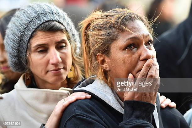 Members of the public stand still at La Belle Equipe cafe on Rue de Charonne one of the places attacked by terrorists on November 16 2015 in Paris...