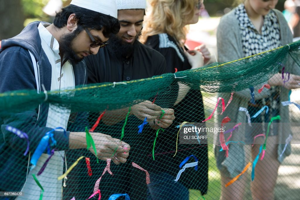 Members of the public symbolically tie ribbons onto a piece of netting during a 'Great Get Together' community service and picnic in memory of murdered Member of Parliament Jo Cox, marking the first anniversary since her killing, in the grounds of All Saints Church in Batley, northern England on June 18, 2017. The Great Get Together weekend is Inspired by murdered Labour MP Jo Cox's belief that we have more in common than which divides us, a line from her first speech to Parliament, and is a community initiative designed to unite people and communities on the streets and parks of their neighbourhoods. The 41 year-old Labour Party MP, Jo Cox, was assassinated by a pro-Nazi sympathiser in a terror attack in her constituency in northern England on June 16, 2016. /