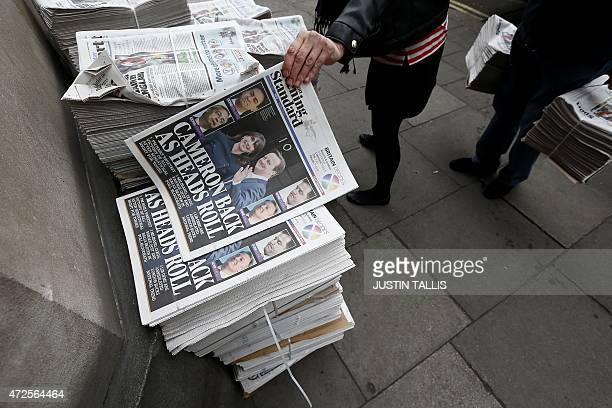 Members of the public take copies of a free newspaper showing election victory for British Prime Minister David Cameron's Conservative Party at a...
