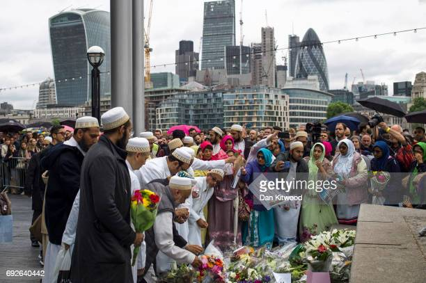Members of the public take part in a vigil for the victims of the London Bridge terror attacks in Potters Fields Park on June 5 2017 in London...