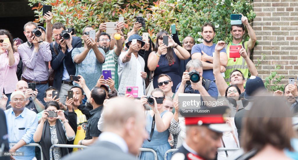 Members of the public take photos as Queen Elizabeth II visits Mayflower Primary School during an official visit to Tower Hamlets on June 15, 2017 in London, England. The visit coincides with commemorations for the centenary of the bombing of Upper North Street School during the First World War.