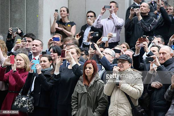 Members of the public take pictures on their smartphones as Queen Elizabeth II and Prince Phillip Duke of Edinburgh arrive at the Lloyds of London...