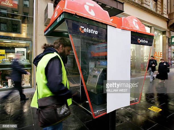 Members of the public use pay phones in Melbourne's Bourke Street mall 11 August 2005 Australian telecommunications giant Telstra Corp Ltd reported...