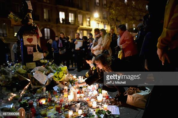 Members of the public view candles and tributes left opposite the main entrance of Bataclan concert hall as French police lift the cordon following...