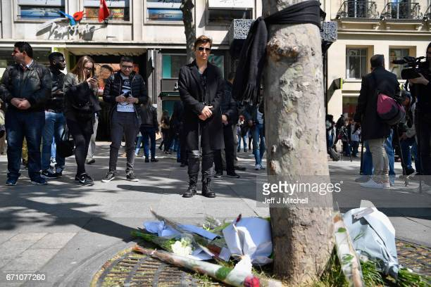 Members of the public view flower near the Marks and Spencer on the Champs Elysees in Paris following yesterday's shooting of a police officer on...