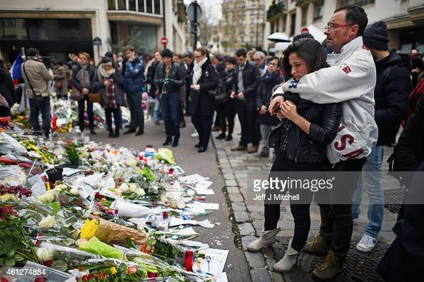 Members of the public view flowers and tributes left near the offices of French satirical magazine Charlie Hebdo on January 10 2015 in Paris France...