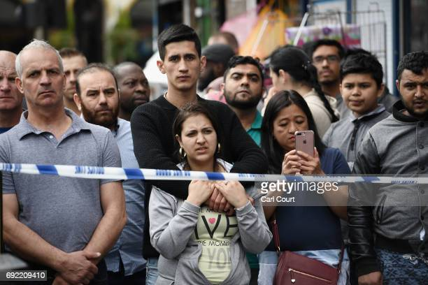 Members of the public view the scene after police officers raided a property in East Ham on June 4 2017 in London England Police have arrested 12...