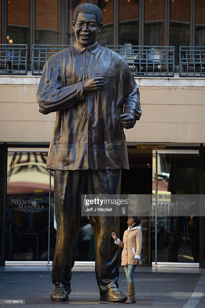 Members of the public visit the Nelson Mandela statue in Sandton on June 17, 2013 in Johannesburg ,South Africa. The former South African President and leader of the anti-apartheid movement is spending a ninth day in hospital and is reported to be responding better to treatment for a recurring lung infection.