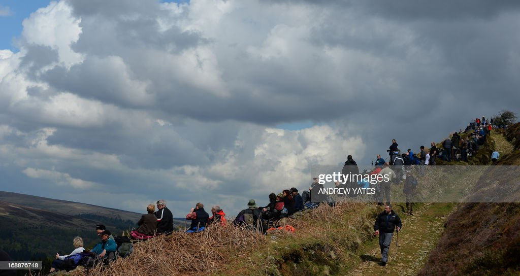 Members of the public wait for a Lancaster bomber to fly over Derwent Reservoir in Derbyshire, England on May 16, 2013, as part of events marking the 70th Anniversary of an air-raid on three dams in Germany's Ruhr Valley by a team of airmen dubbed the 'Dambusters'. A British World War II Lancaster bomber performed a flypast over a reservoir used for practice runs by the legendary 'Dambusters' airmen to mark 70 years since their daring raid over Nazi Germany's industrial heartland. The four-engined aircraft was joined by two Spitfires and two modern-day Tornado jets as they swept over the Derwent Reservoir in Derbyshire, northern England, where the Royal Air Force trialled the 'bouncing bomb'. AFP PHOTO/ANDREW YATES