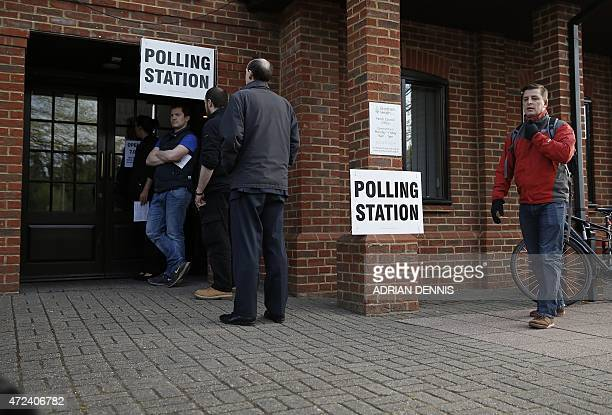 Members of the public wait to cast their votes at a polling station in Elvetham Heath in southern England on May 7 as Britain holds a general...