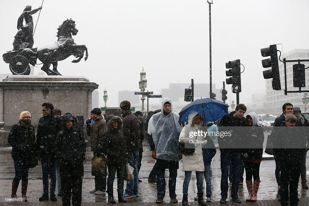 Members of the public wait to cross the road at the end of Westminster Bridge as snow falls on January 18, 2013 in London, England. Widespread snowfall is affecting most of the UK with school closures and transport disruption. The Met Office has issued a red weather warning for parts of Wales, advising against all non-essential travel as up to 30cm of snow is expected to fall in some areas today..