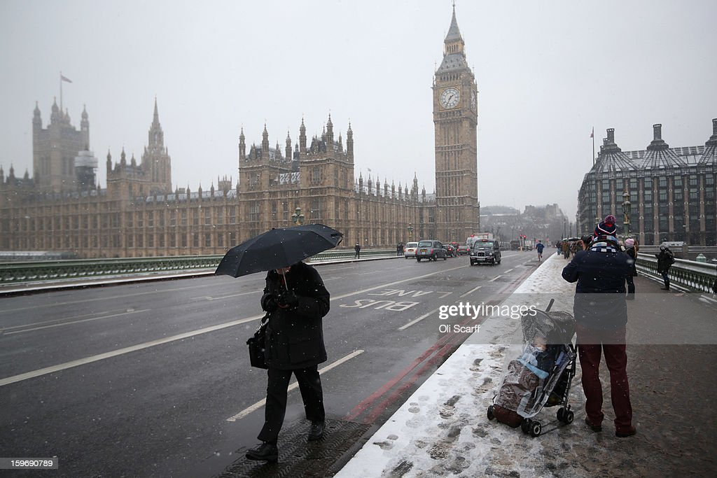 Members of the public walk across Westminster Bridge as snow falls on January 18, 2013 in London, England. Widespread snowfall is affecting most of the UK with school closures and transport disruption. The Met Office has issued a red weather warning for parts of Wales, advising against all non-essential travel as up to 30cm of snow is expected to fall in some areas today..