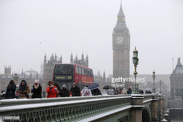 Members of the public walk across Westminster Bridge as snow falls on January 18 2013 in London England Widespread snowfall is affecting most of the...