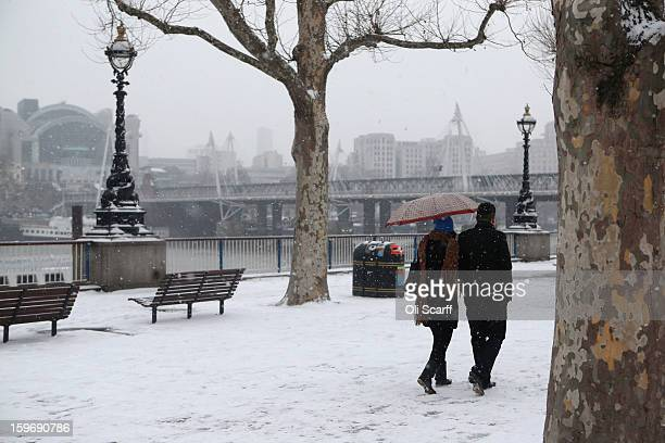 Members of the public walk along the South Bank of the river Thames as snow falls on January 18 2013 in London England Widespread snowfall is...