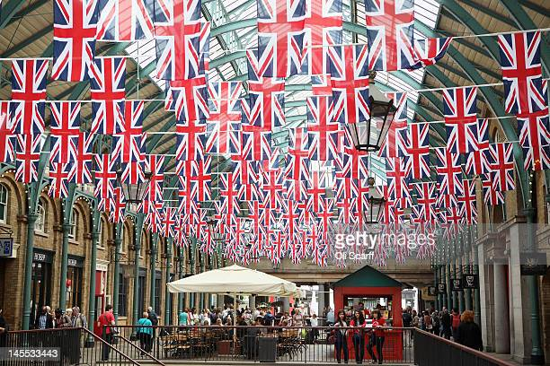 Members of the public walk beneath Union Flags displayed to celebrate the Diamond Jubilee of Her Majesty Queen Elizabeth II in Covent Garden on June...