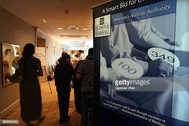 Members of the public walk into an auction held by Hudson Marshall for more than 25 foreclosed homes at the Renaissance Newark Airport Hotel on June...