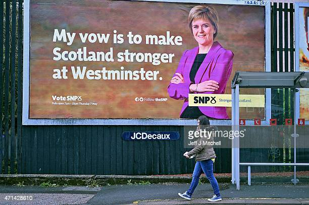 Members of the public walk past a billboard of First Minister of Scotland and leader of the SNP Nicola Sturgeon on the South Side on April 28 2015 in...