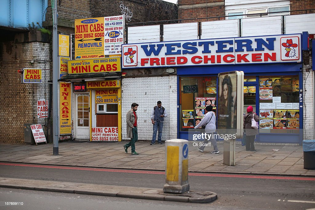 Members of the public walk past a mini-cab kiosk and a fst food fried chicken outlet near Lewisham high street on December 5, 2012 in London, England. The Chancellor of the Exchequer George Osborne has stated that the United Kingdom's economy is still struggling during his autumn budget statement to Parliament.