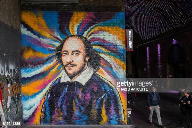 Members of the public walk past a mural of William Shakespeare by graffiti artist James Cochran aka Jimmy C on Clink Street near the Shakespeare's...