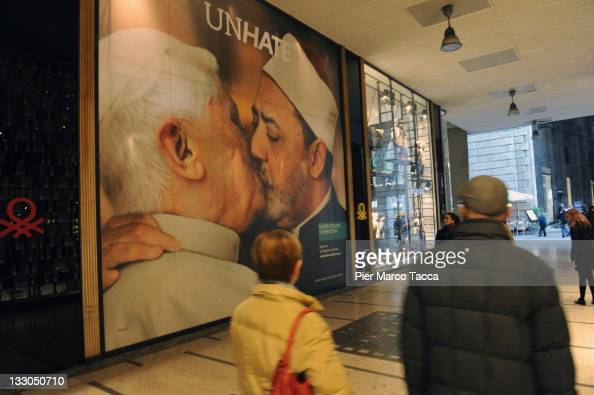 Members of the public walk past a new Benetton advertising poster campaign displayed on a wall on November 16 2011 in Milan Italy  The posters part...