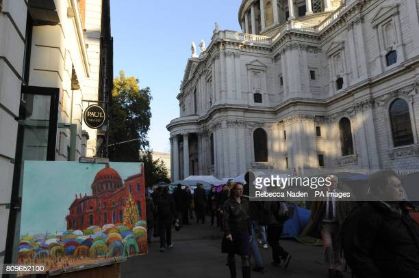 Members of the public walk past a painting depicting the tents of anticapitalist protesters who have been camped outside St Paul's Cathedral for a...