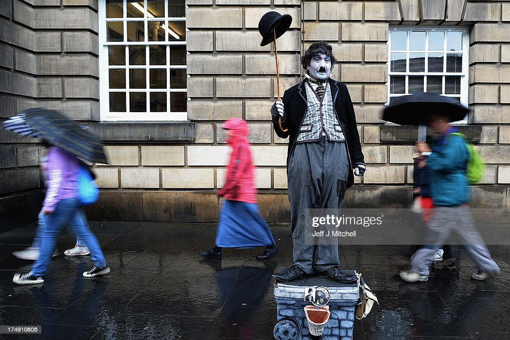 Members of the public, walk past a street entertainer on the Royal Mile on July 29, 2013 in Edinburgh, Scotland. The city is preparing ahead of the Edinburgh Fringe Festival which runs from the 2 -26 August and is one of the largest arts festivals in the world, dating back to 1947. The festival attracts thousands of performers from across the world to showcase their acts in Scotland's capital.