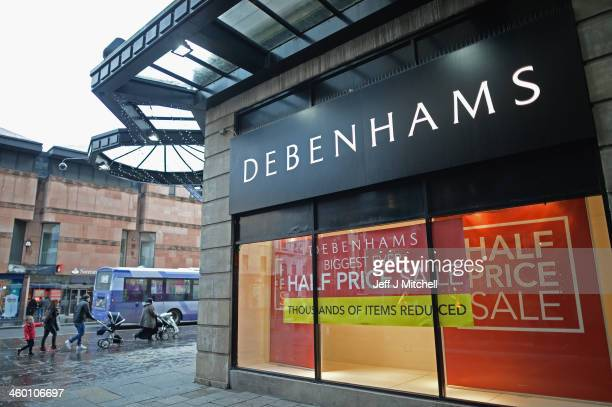 Members of the public walk past Debenhams store as companies announce Christmas sales results on January 2 2014 in Glasgow United KingdomShares in...