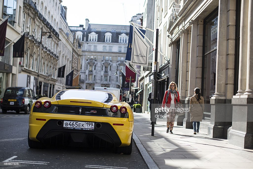 Members of the public walk past luxury goods retailers and a yellow Lamborghini on Old Bond Street on April 15 2014 in London England A report by...