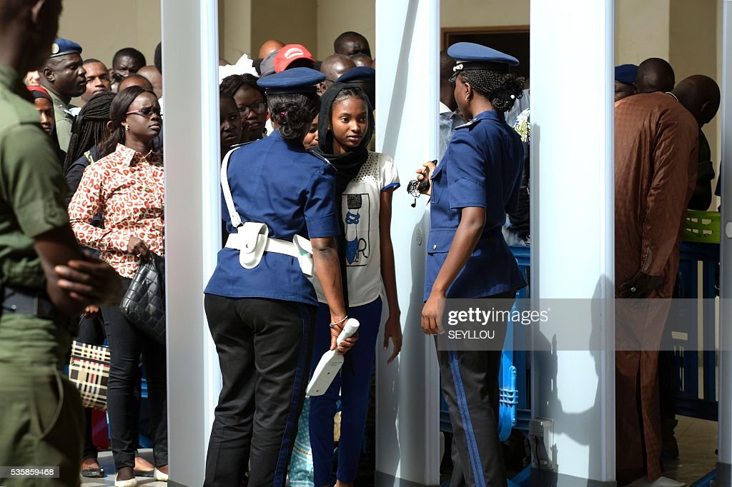 Members of the public walk through a security check point as they enter the Dakar courthouse to attend the sentencing of former Chadian dictator Hissene Habre on May 30, 2016 in Dakar, Senegal. Former Chadian dictator Hissene Habre was found guilty of crimes against humanity and sentenced to life in prison by a special court in Senegal on May 30, 2016. The case, at the Extraordinary African Chambers (CAE) - a special tribunal set up by the African Union under a deal with Senegal - is the first time a country has prosecuted a former leader of another nation for rights abuses. / AFP / SEYLLOU