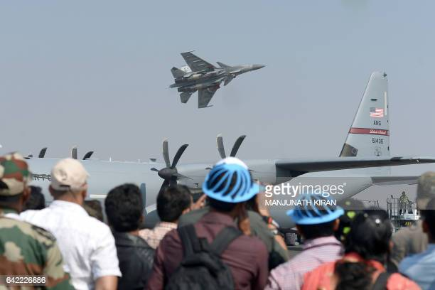 Members of the public watch a Sukhoi Su30 MKi multirole combat aircraft of the Indian Air Force take off for an aerial display on the fourth day of...