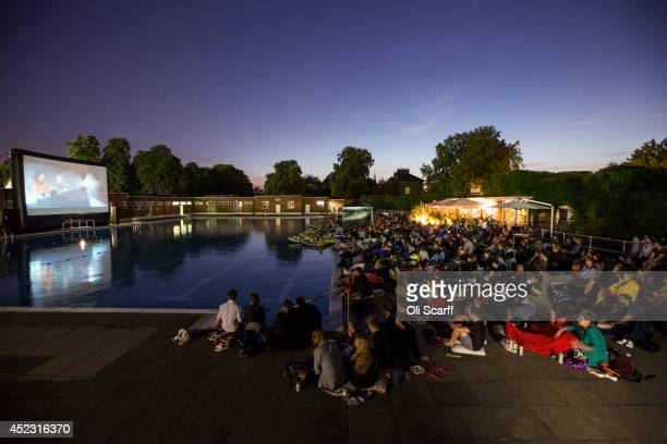 Members of the public watch an outdoor screening of the film 'Jaws' in Brockwell Lido at night on July 17 2014 in London England The outdoor...