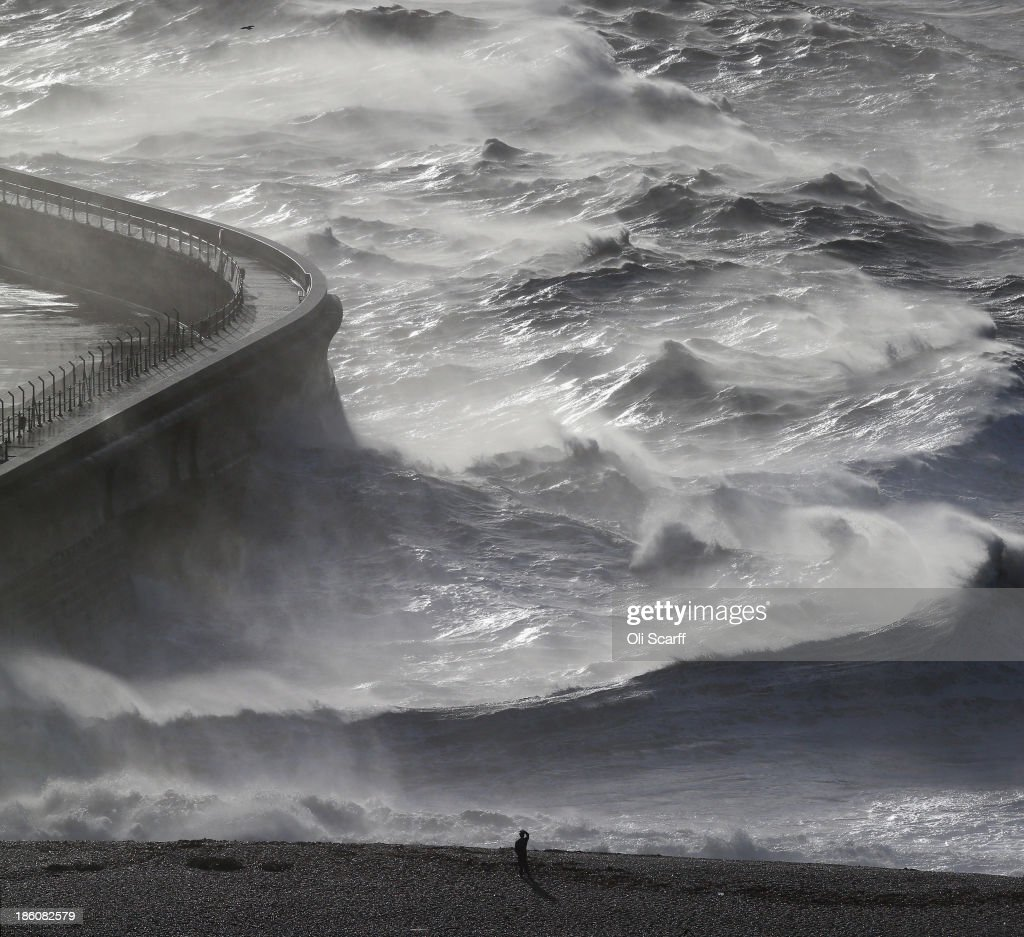 Members of the public watch as large waves, produced by storm force winds, break against the harbour wall on October 28, 2013 in Dover, England. Approximately 220,000 homes are without power and two deaths have been recorded after much of southern England has been affected by a severe storm. Transport links on road, rail, air and sea have been severely disrupted by hurricane-force winds that have almost reached 100 mph in places.