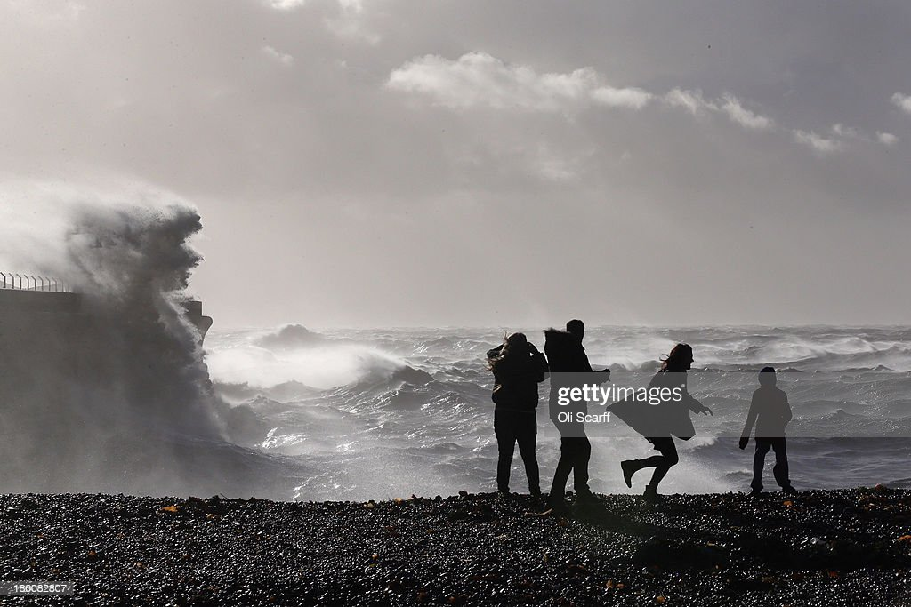 Members of the public watch as large waves, produced by storm force winds, break against the harbour wall on October 28, 2013 in Dover, England. Approximately 220,000 homes are without power and two deaths have been recorded after much of southern England has been affected by a severe storm. Transport links on road, rail, air and sea have been severely disrupted by hurricane-force winds that have almost reached 100 mph in places..