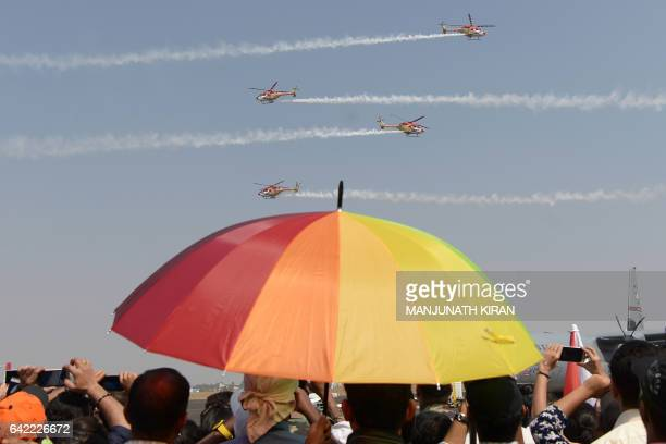 Members of the public watch Sarang helicopters perform manoeuvres during an aerial display on the fourth day of the 11th edition of 'Aero India' a...