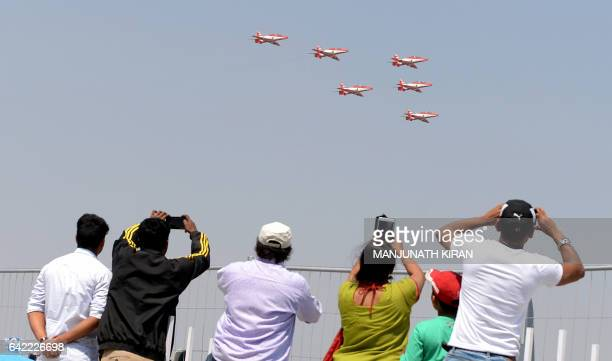 Members of the public watch Surya Kiran aerobatic team perform manoeuvres during an aerial display on the fourth day of the 11th edition of 'Aero...