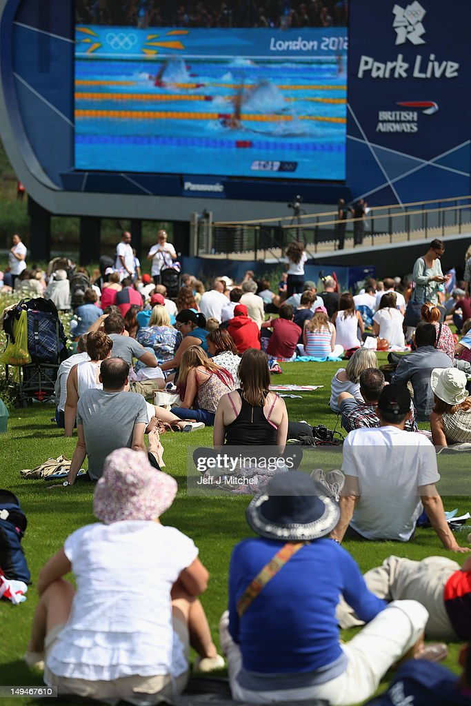 Members of the public watch swimming on a big screen on day one of the London 2012 Olympic Games at the Olympic Park on July 28, 2012 in London, England.
