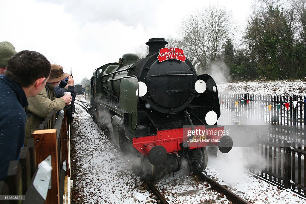 Members of the public welcome the Grinsteade Belle as it arrives at East Grinstead Station for the first time on March 23, 2013 in East Grinstead, England. The Bluebell Railway ran its first steam train this weekend on the reclaimed line from Kingscote to East Grinstead after volunteers from the Bluebell Society worked to reopen the line after its closure on March 17, 1958. 50 years on from Dr. Richard Beeching's report signaling the widespread closure of rural rail routes across the UK, Britain's railways are in great demand with old lines reopening and pressure on to restore rural lines that were closed.