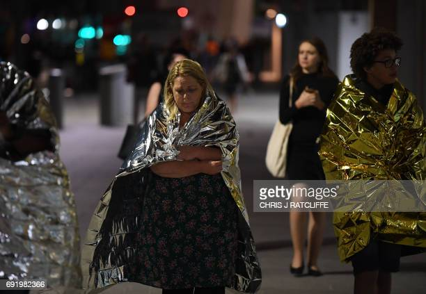TOPSHOT Members of the public wrapped in emergency blankets leave the scene of a terror attack on London Bridge in central London on June 3 2017...