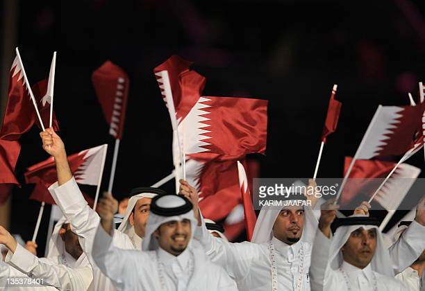 Members of the Qatari team wave national flags during the opening ceremony of the panArab Games in the Gulf emirate's capital Doha on December 9 2011...