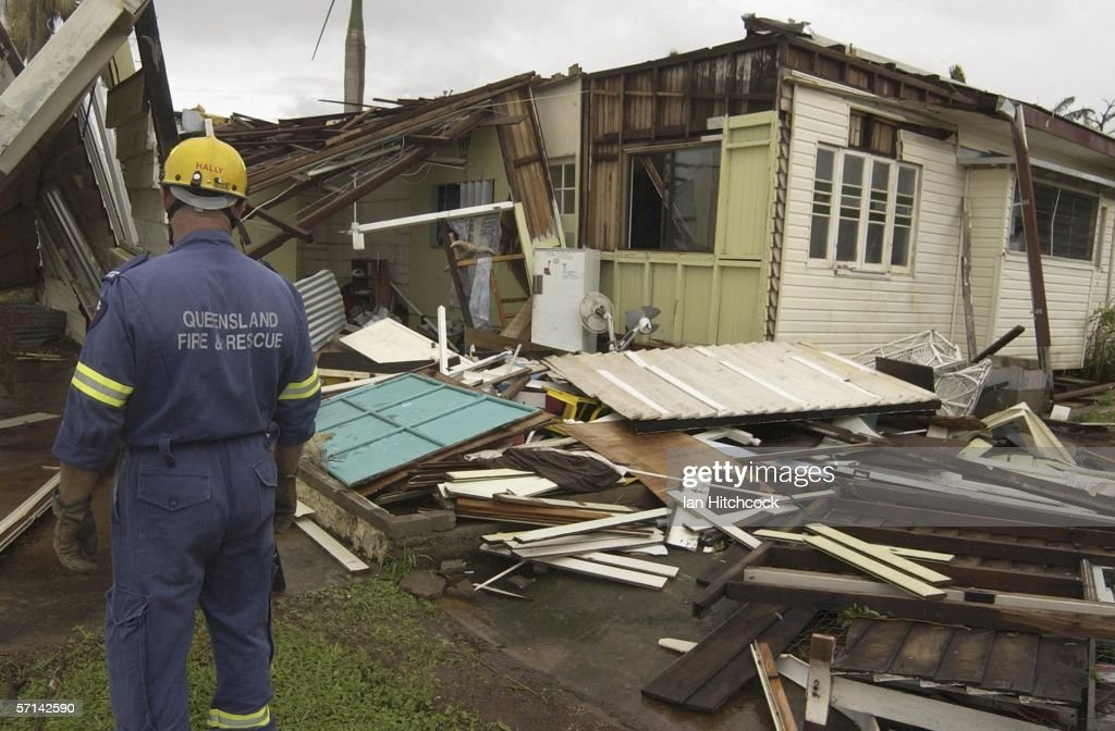 Members of the Queensland Fire and Rescue search a house badly damaged by tropical cyclone Larry in South Johnston March 21 2006 just outside...
