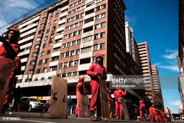 Members of the Red Ants a municipal team tasked with evictions line up outside the Fattis Mansion in downtown Johannesburg on July 19 2017 Residents...