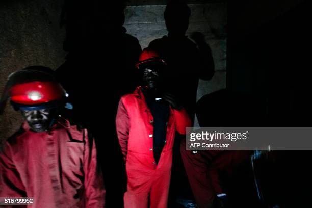 Members of the 'Red Ants' a municipal team tasked with evictions look on during an eviction inside the Fattis Mansion in Johannesburg on July 19 2017...