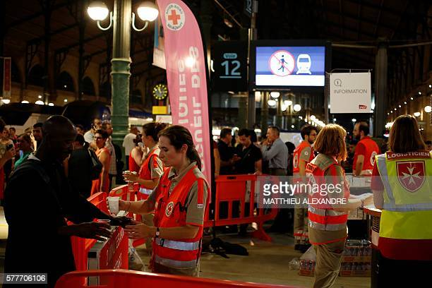 Members of the Red Cross and of the humanitarian nongovernmental organization Order of Malta France give water to people waiting at the Gare du Nord...