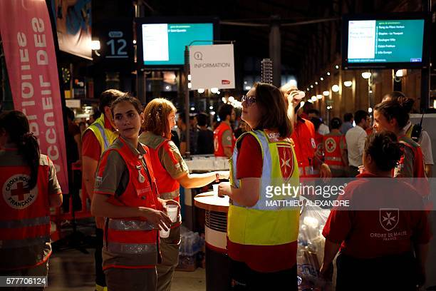 Members of the Red Cross and of the humanitarian nongovernmental organization Order of Malta France hold glasses of water before giving it to people...