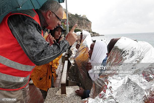 Members of the Red Cross arrive to give breakfast to migrants gathered on the rocks off the coast of Ventimiglia Italy on June 14 2015 after having...