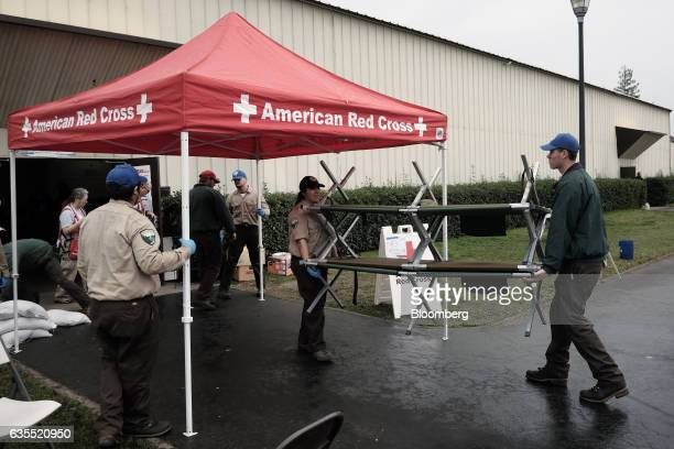 Members of the Red Cross carry cots at the Silver Dollar Fairgrounds evacuation center in Chico California US on Wednesday Feb 15 2017 Crews worked...