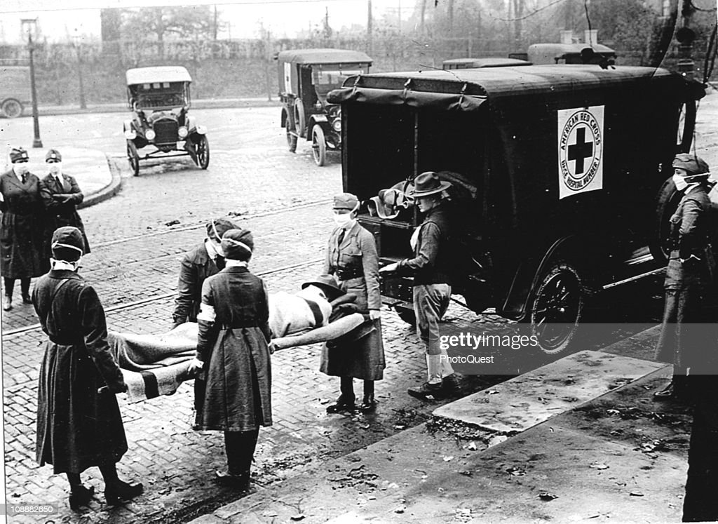 Members of the Red Cross Motor Corps all wearing masks against the further spread of the influenza epidemic carry a patient on a stretcher into their...