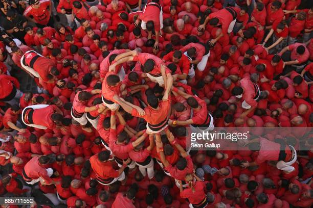 Members of the red team climb over their colleagues who form the dense base in order to build the first tiers of their human tower during the St...